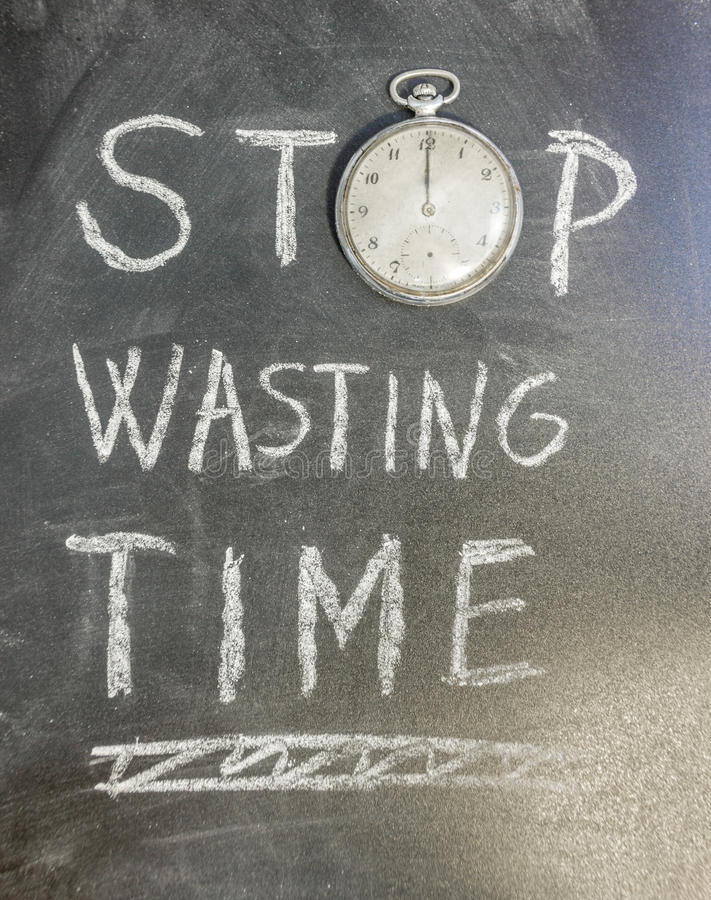Stop Wasting Time. Wasting time concept on chalk table whit an old pocket watch stock photos