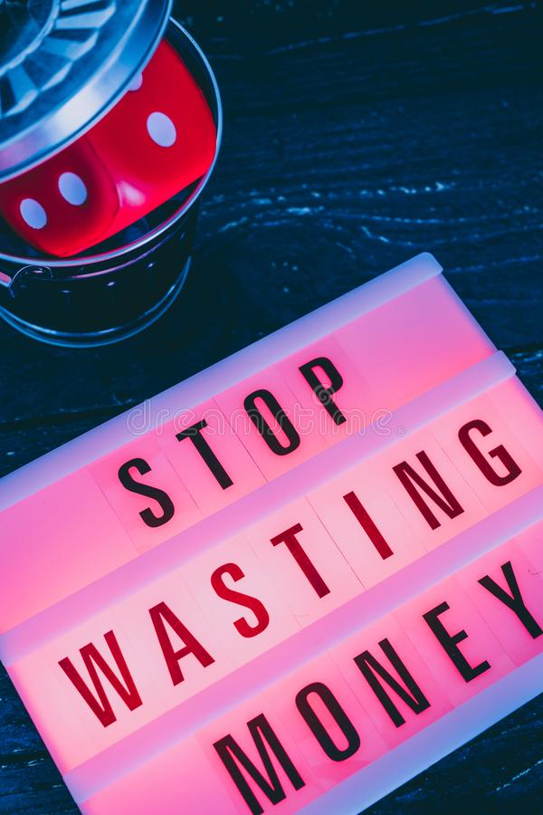 Stop wasting your money message on lightbox with gambilng dice thrown in the bin stock images