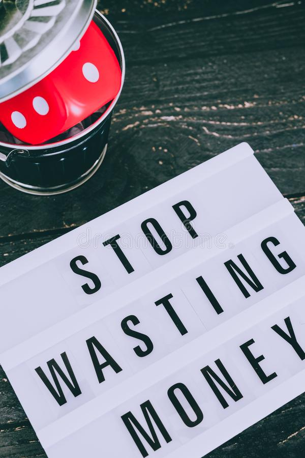Stop wasting your money message on lightbox with gambilng dice thrown in the bin royalty free stock photo