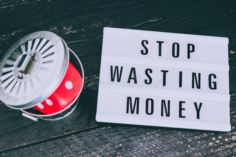 Stop wasting your money message on lightbox with gambilng dice thrown in the bin stock photo