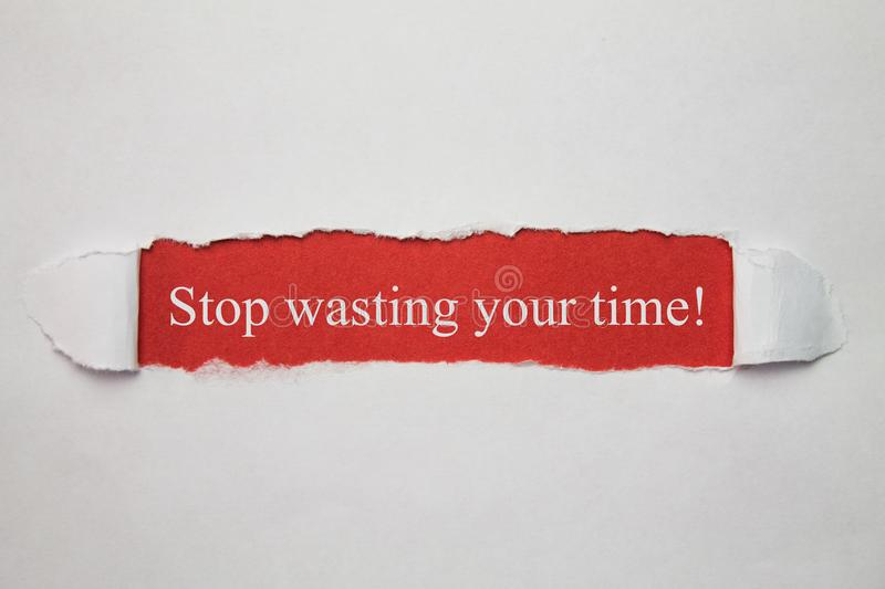 Stop wasting your time word on a torn paper. stock photography