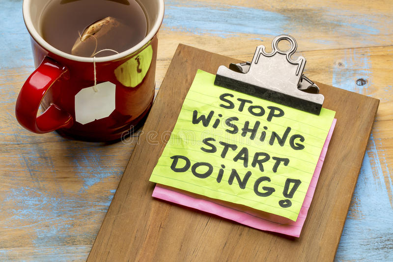 Stop wishing, start doing advice. Stop wishing, start doing motivational - a sticky note on a clipboard against grunge wood grunge wood table stock photo