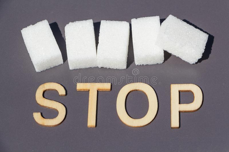 Stop to sugar. Stop in wooden letters and sugar cubes, concept to stop eating too much sugar royalty free stock images