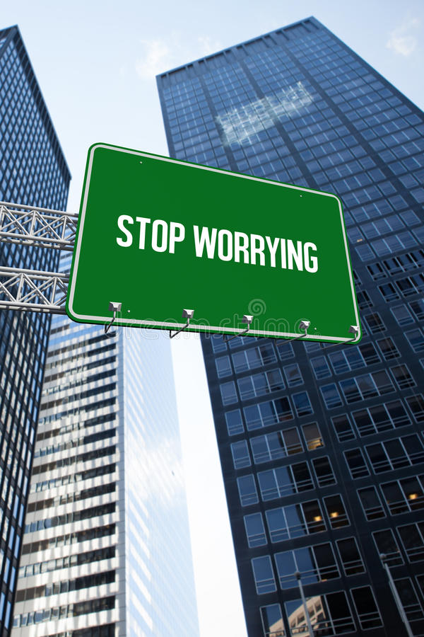 Stop worrying against low angle view of skyscrapers. The word stop worrying and green billboard sign against low angle view of skyscrapers royalty free stock image