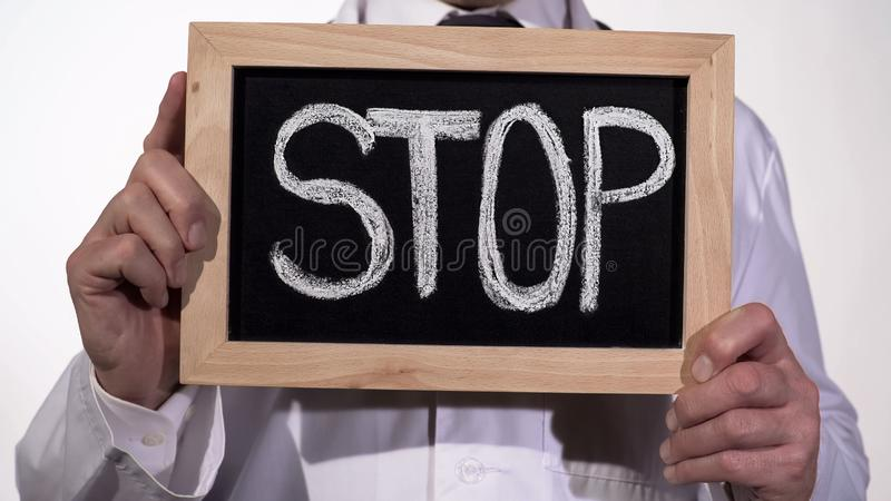 Stop written on blackboard in doctor hands, fight against harmful bad habits. Stock footage royalty free stock photography