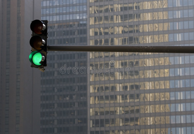 Stoplight Against Building. Green stoplight with a glass and concrete building in the background stock image
