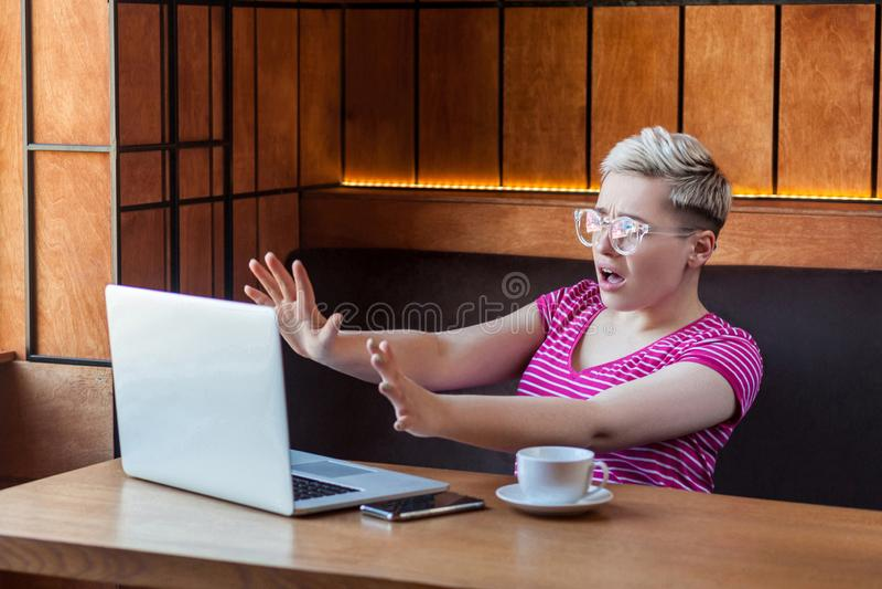 Stopp! Ståenden för sidosikten av den emotionella förskräckta ung flickafreelanceren sitter i kafé, och att skrika till laptopeor royaltyfria foton