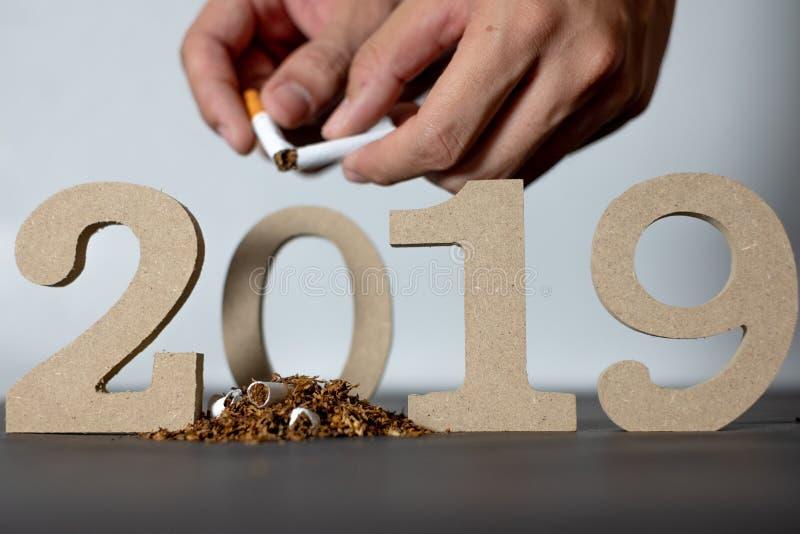 Stoppa att röka 2019 och att röka upphörandedagen 2019 på en svart bakgrund och händer som förstör cigaretter arkivfoton