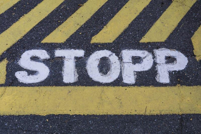 Stoppa tecknet STOPP i svensk som målas på asfalt fotografering för bildbyråer