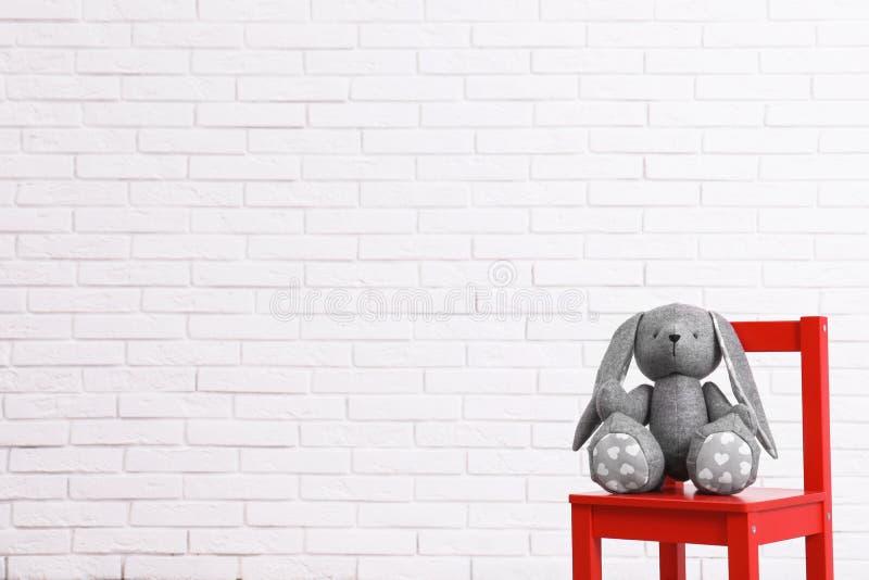 Stoppad leksakkanin på stol mot den vita väggen, utrymme för text Inre detaljer för barnrum arkivbild