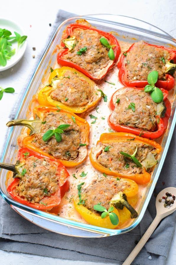 Stoppade peppar med kött, grönsaker och krämig tomatsås arkivbilder