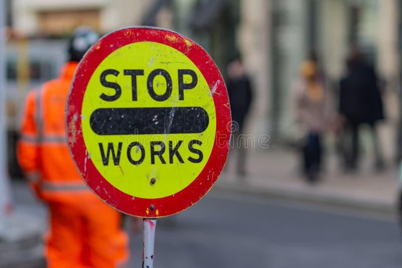Stopparbeten för varnande tecken och en man i orange arbete i bakgrund på gatan som fotograferas med grunt djup av fältet royaltyfri fotografi