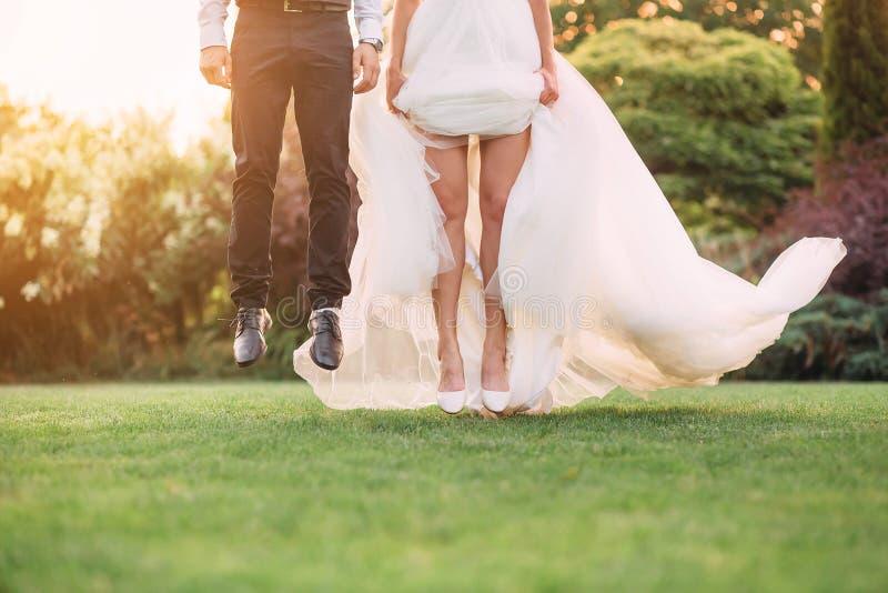 Stoppat ögonblick ett hopp i luften som, om bruden och brudgummen flyger ovanför det gröna gräset i trädgården, inga framsidor på arkivfoton