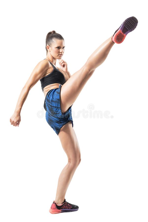 Stopped action motion of tough woman kickboxing fighter doing high kick royalty free stock images