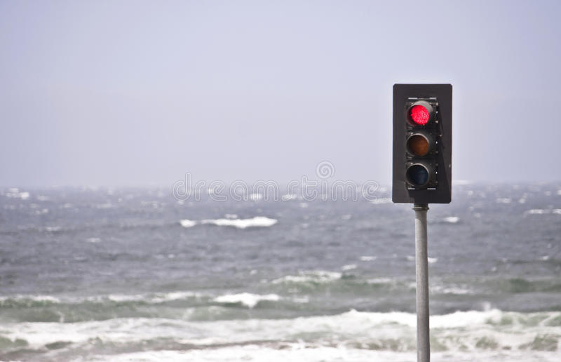 Stopped at the Sea. A traffic light that is red, in front of the ocean stock photos