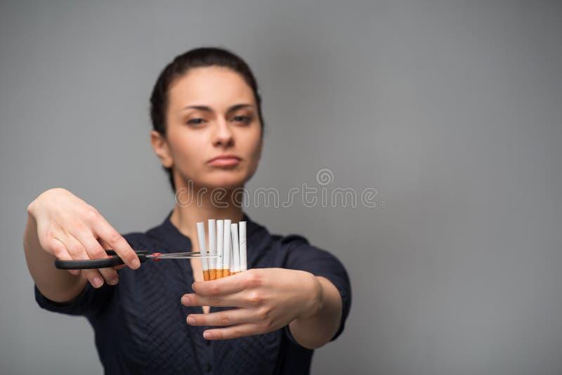 Stoppen Sie, Konzept zu rauchen Schnittzigaretten der jungen Frau stockfotografie