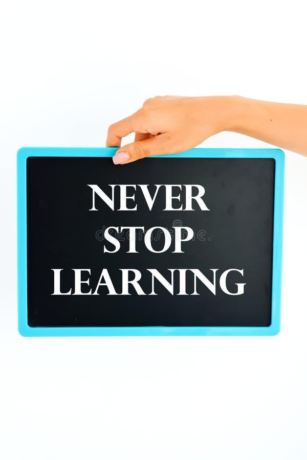 Stoppen Sie nie das Lernen, das auf kleine Tafel in Frauenhand geschrieben wird lizenzfreies stockbild