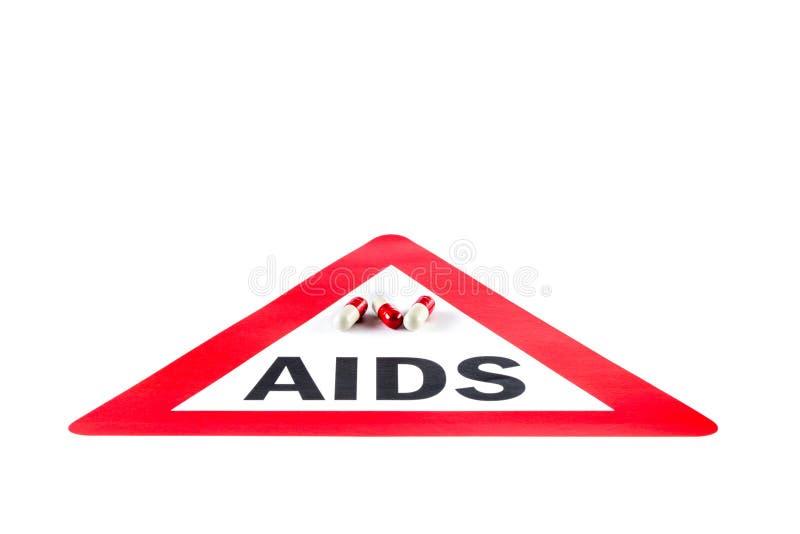 StoppHJÄLPMEDEL och HIV, kapsel med varningstecknet arkivfoton