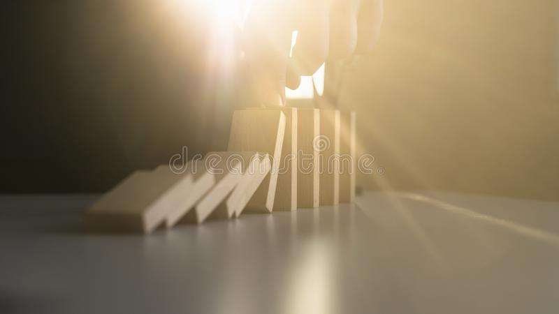 Stopping domino effect with a bright light flare from behind royalty free stock photo