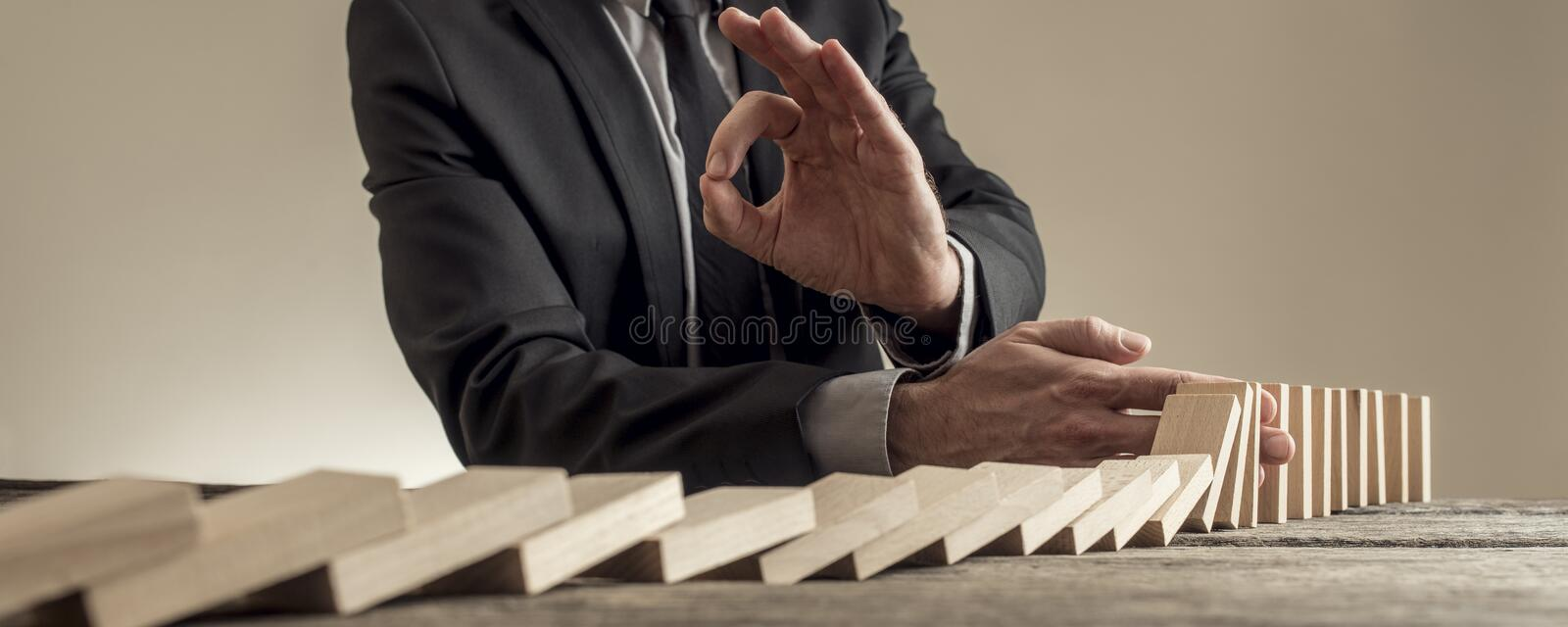Stopping dominoes row from crumbling and showing Ok gesture. Low wide angle view of man in business clothes stopping dominoes row from crumbling and showing Ok stock image