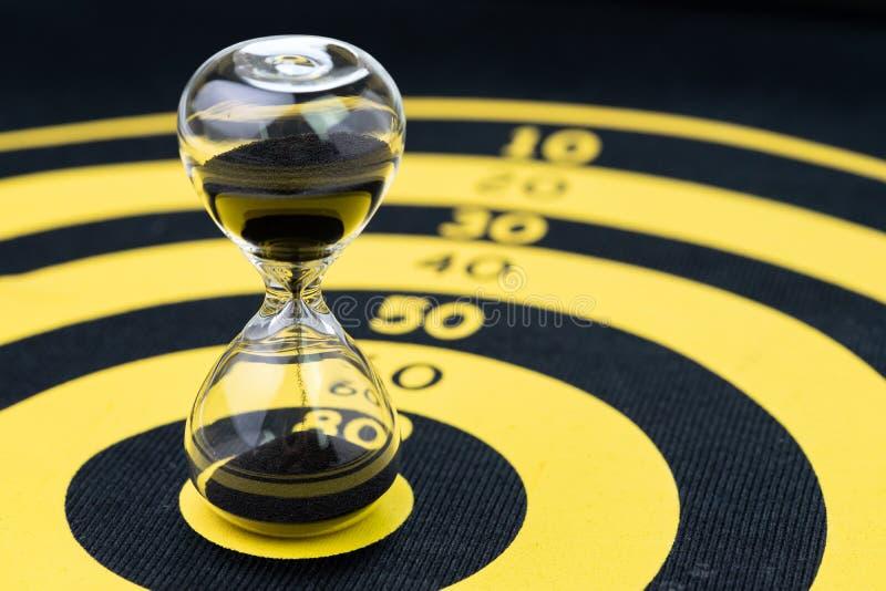 Stopptid, tidledning eller mål och mål med begrepp, timglas eller sandglass för tid specifikt på gul cirkeldarttavla arkivbilder