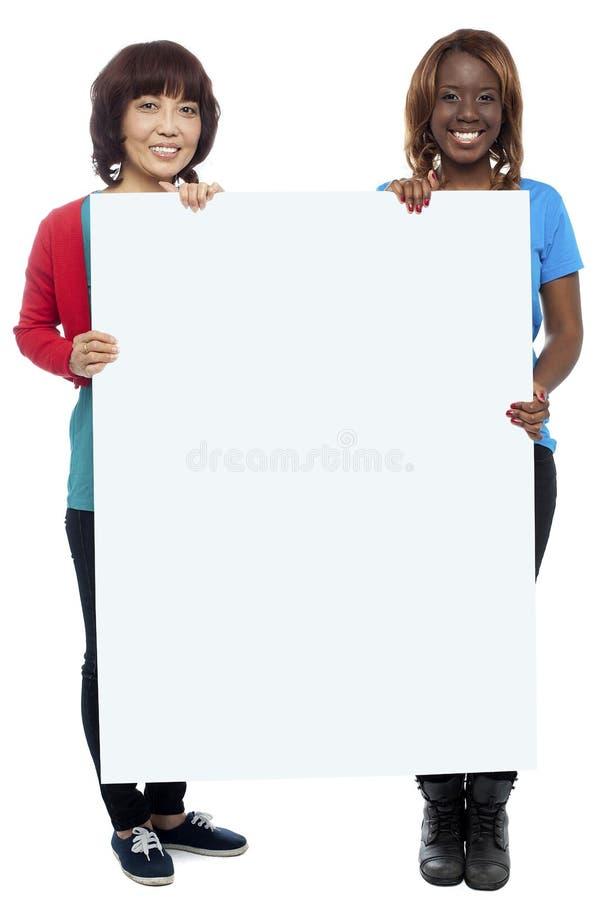 Stor affischtavla som presenteras av tillfälliga flickor arkivbilder