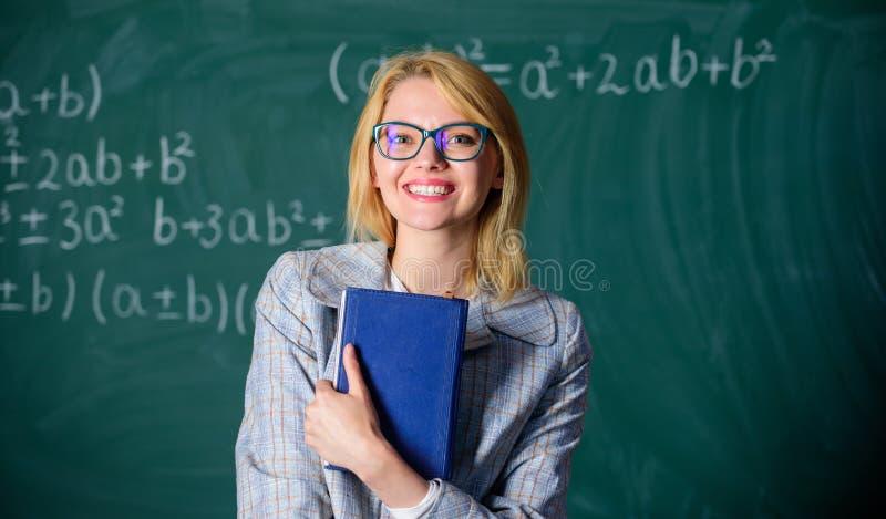 Stor bokstav av rekommendationen Kvinna som ler den svart tavlan för framdel för ställning för lärarehållbok Rekommendation för h royaltyfri foto