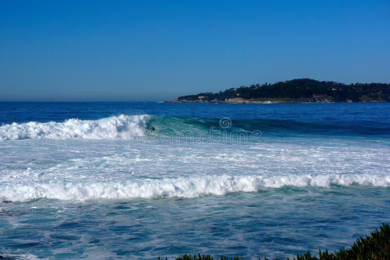 Stor bränning ställa i skuggan surfaren arkivfoto