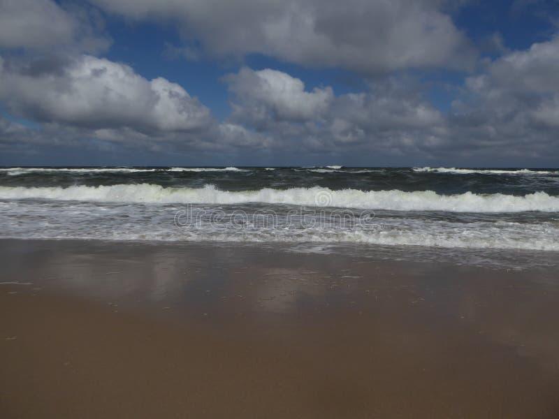 Stor brytande havvåg på en sandig strand på det baltiska havet i Polen arkivfoto