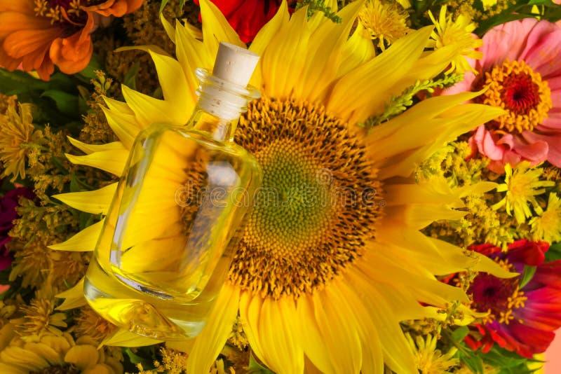 Stor bukett med solrosen och den lilla flaskan med olja arkivbild
