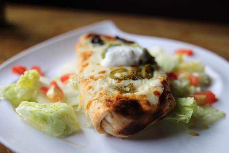 Stor Burrito på en vit platta arkivbild