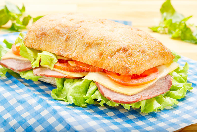 Stor Ciabatta smörgås med bacon, grönsallat, tomat, ost royaltyfri bild