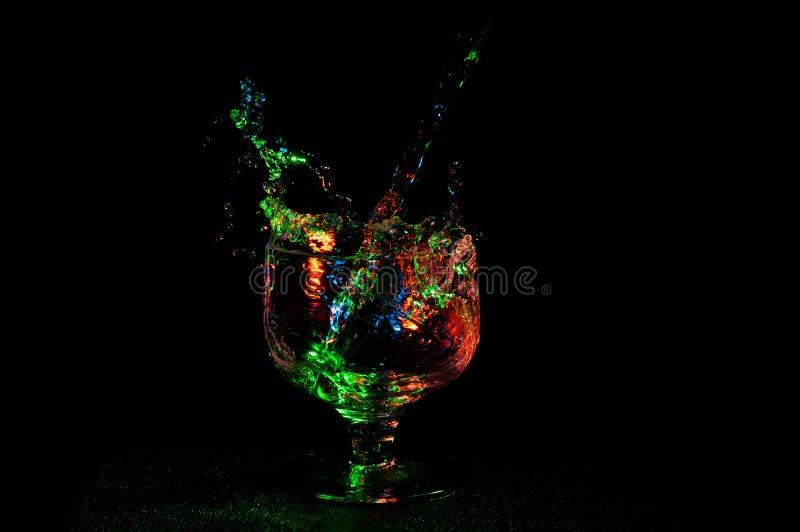 Stor färgrik färgstänk av flytande i ett konjakexponeringsglas fotografering för bildbyråer