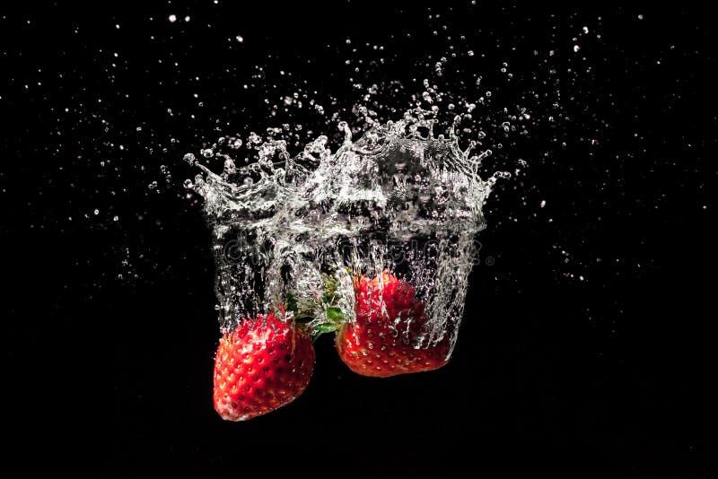Stor färgstänk för jordgubbefrukt in i vatten arkivfoton