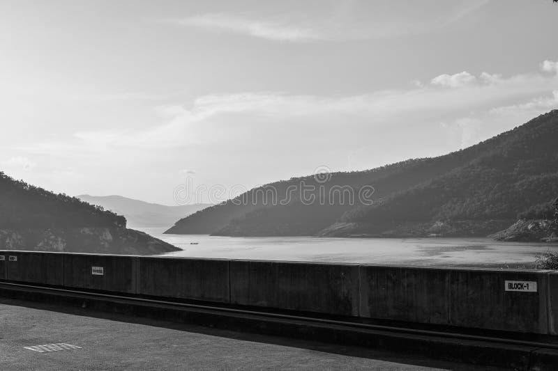 Stor fördämning med berget som omges i svartvitt arkivfoton