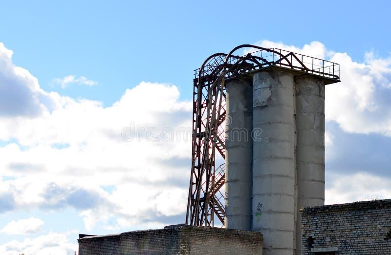 Stor förstärkt konkret rörkonstruktion med en metallstege mot en ljus blå himmel royaltyfri bild