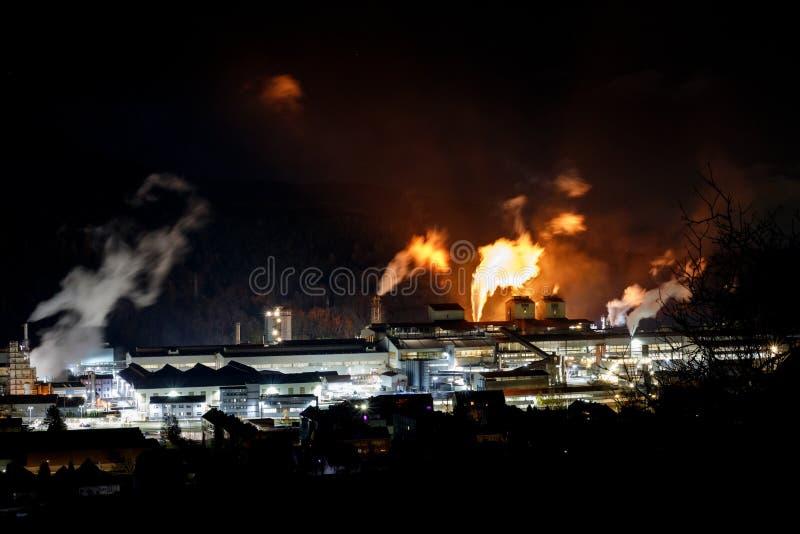 Stor fabrik på natten med brand och ljus arkivfoto