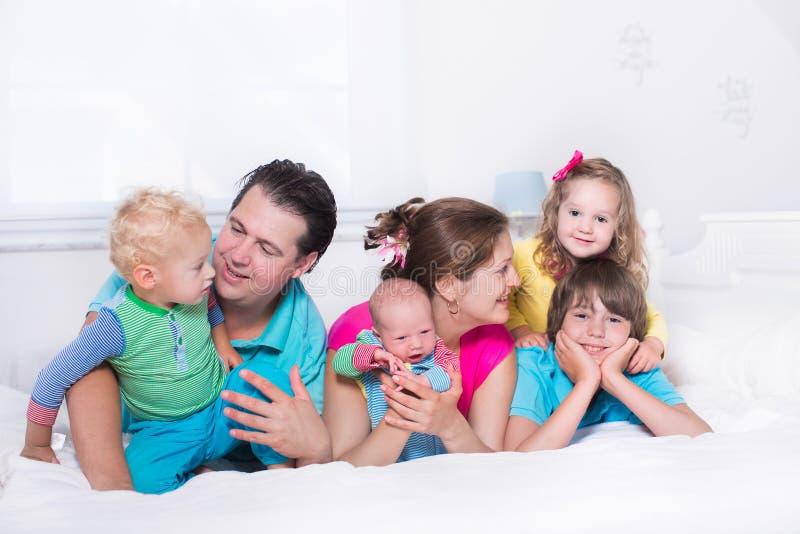 Stor familj med ungar i säng royaltyfria foton