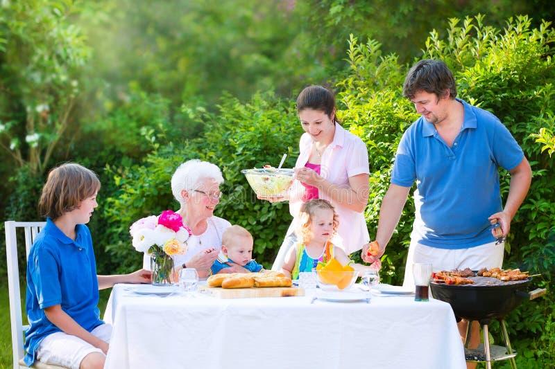 Stor familj som grillar kött för lunch på solig dag royaltyfri foto