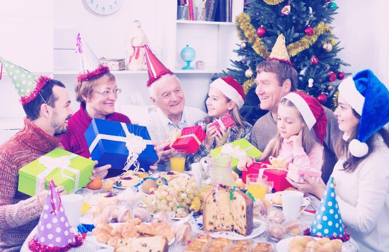 Stor familj som till varandra räcker gåvor royaltyfri foto