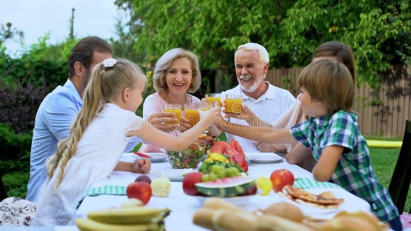 Stor familj som tillsammans klirrar fruktsaftexponeringsglas och att ha matställen, icke-alkohol parti arkivbild