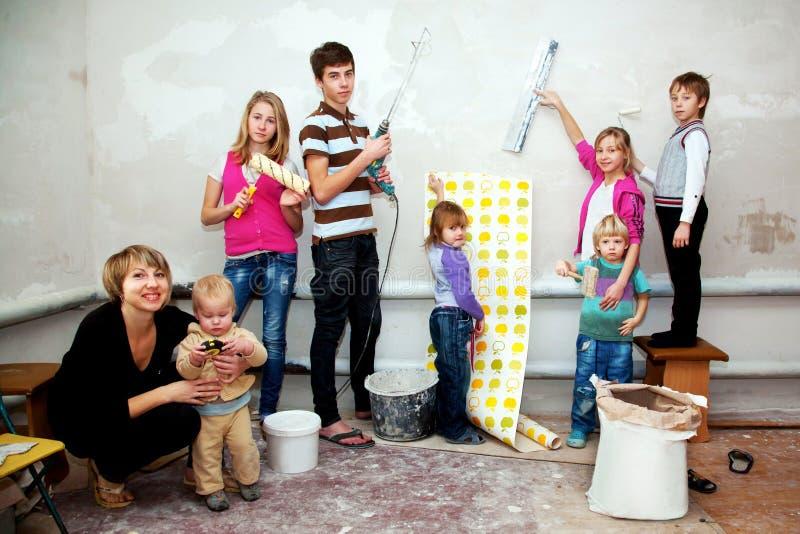 Stor familjdanande reparerar till deras nya hem. arkivbild