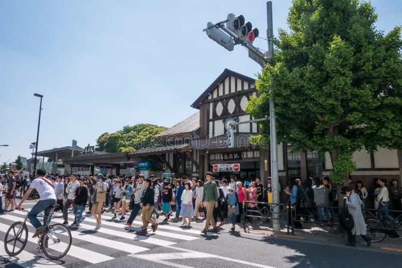 Stor folkmassa av folk som går ut ur den Harajuku stationen i guld- vecka royaltyfri bild
