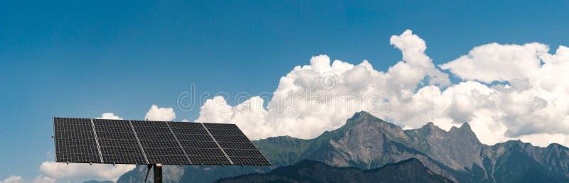 Stor fristående solpanel med panoramaberglandskap i de schweiziska fjällängarna royaltyfri foto