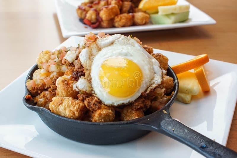 Stor frukost med stekte ägg, tatersmå barn, tomaten och den kryddiga nötköttnachoblandningen royaltyfria bilder