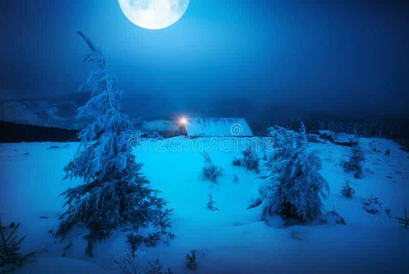 Stor fullmåne ovanför vinterbyn royaltyfria foton