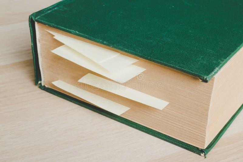 Stor gammal bok med etikettssidor vid gula klibbiga anmärkningar arkivfoto
