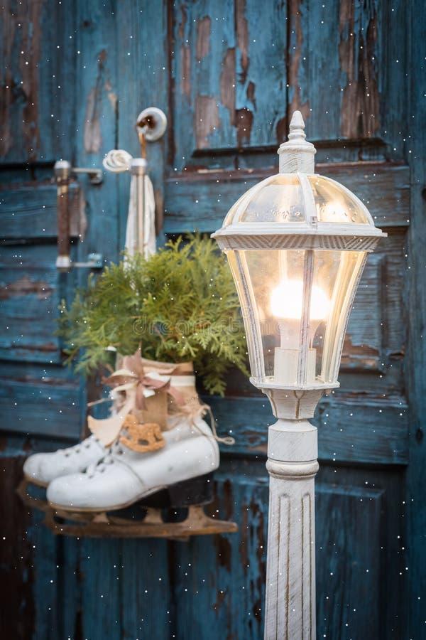 Stor gammal lykta och ett par av vita isskridskor för tappning med julgarnering som hänger på den blåa lantliga dörren royaltyfri bild