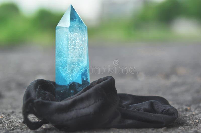 Stor genomskinlig mystisk fasetterad kristall av kulör blå safir, topas på en underbar mineralisk kvarts för ljus bakgrundsnärbil royaltyfri fotografi