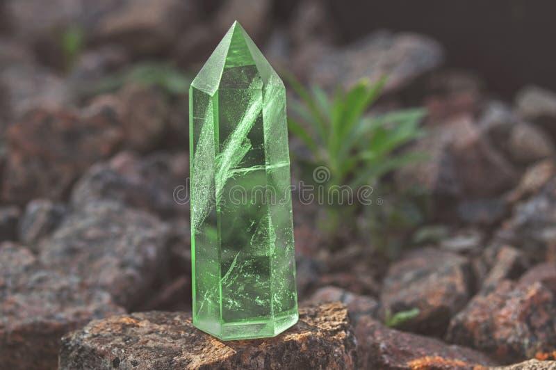 Stor genomskinlig mystisk fasetterad kristall av kulör grön smaragdkvarts på en stenbakgrundsnärbild Underbar mineral royaltyfri foto